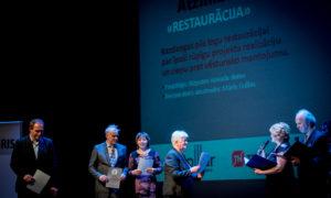 """""""Restaurācija"""", atzinība. LRB valdes priekšsēdētāja Dace Čoldere. Juris Moisejs, Kazdangas pagasta pārvaldes vadītājs, Biruta Konrāde, Aizputes novada domes Attīstības nodaļas projektu vadītāja, restaurators Māris Gulbis."""