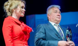 """Olga Fiļ, """"Beaux Art"""" vadītāja, saņem dizaina ikonu """"Anna Gong"""" no """"Alessi"""" par nozīmīgu ieguldījumu būvniecībā. Pasniedz konkursa atbalstītāja """"Abora"""" vadītājs Juris Kravalis."""