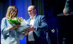 """Konkursa atbalstītāja """"Baumit"""" pārstāvis Raimonds Rudzītis pasniedz specbalvu dizainerei Dacei Baidekalnei."""
