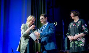 """Anda Munkevica, """"AM Studio"""" vadītāja, saņem balvu par nozīmīgiem sasniegumiem dizaina veicināšanā, pasniedz konkursa atbalstītāja """"Būvuzraugi.LV"""" vadītājs Sergejs Frolovs un Māra Lāce, LNMM direktore."""